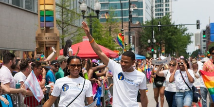 Robert Emmons Jr. waves to supporters, while walking with his wife Brittani Emmons, left, at the 2019 Chicago Pride Parade on June 30, 2019.