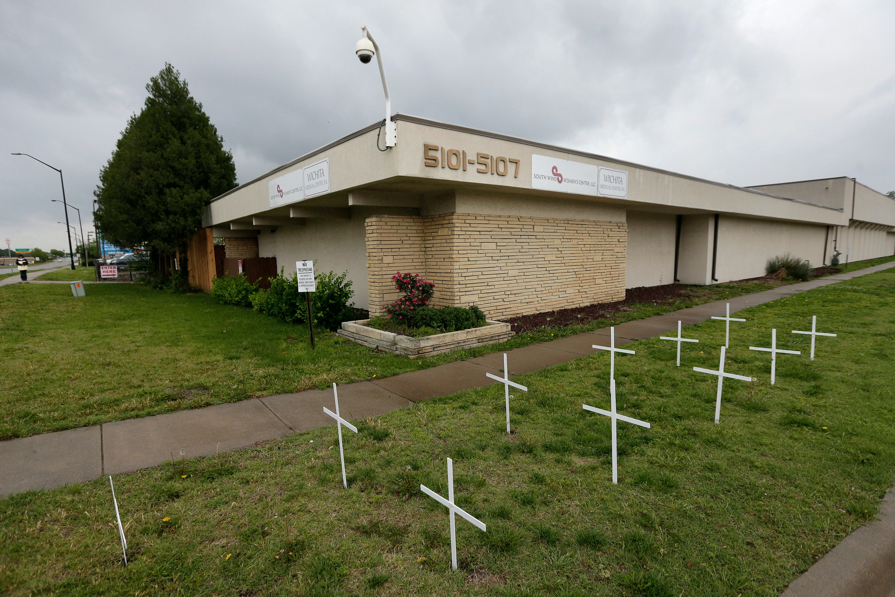 In this photo taken Thursday, May 19, 2016, crosses placed by anti-abortion protesters stand in the lawn outside the South Wind Women's Center in Wichita, Kan. Julie Burkhart, the executive director at the clinic, has vowed to keep the facility open through planned protests this summer marking the 25th anniversary of the 1991 Summer of Mercy protests that led to nearly 2,700 arrests at this and other clinics in Wichita. (AP Photo/Charlie Riedel)