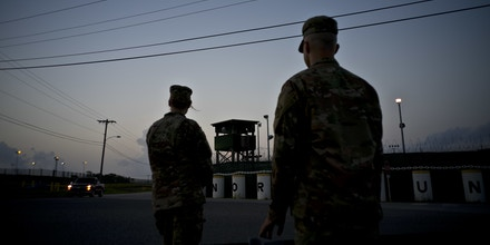 In this Tuesday, June 5, 2018 photo, reviewed by U.S. military officials, troops stand guard outside Camp Delta at the Guantanamo Bay detention center, in Cuba. The Pentagon has asked Congress to approve money for a new super-max prison unit to be designed with the understanding that prisoners will grow old and frail in custody, some perhaps still without being convicted of a crime. (AP Photo/Ramon Espinosa)