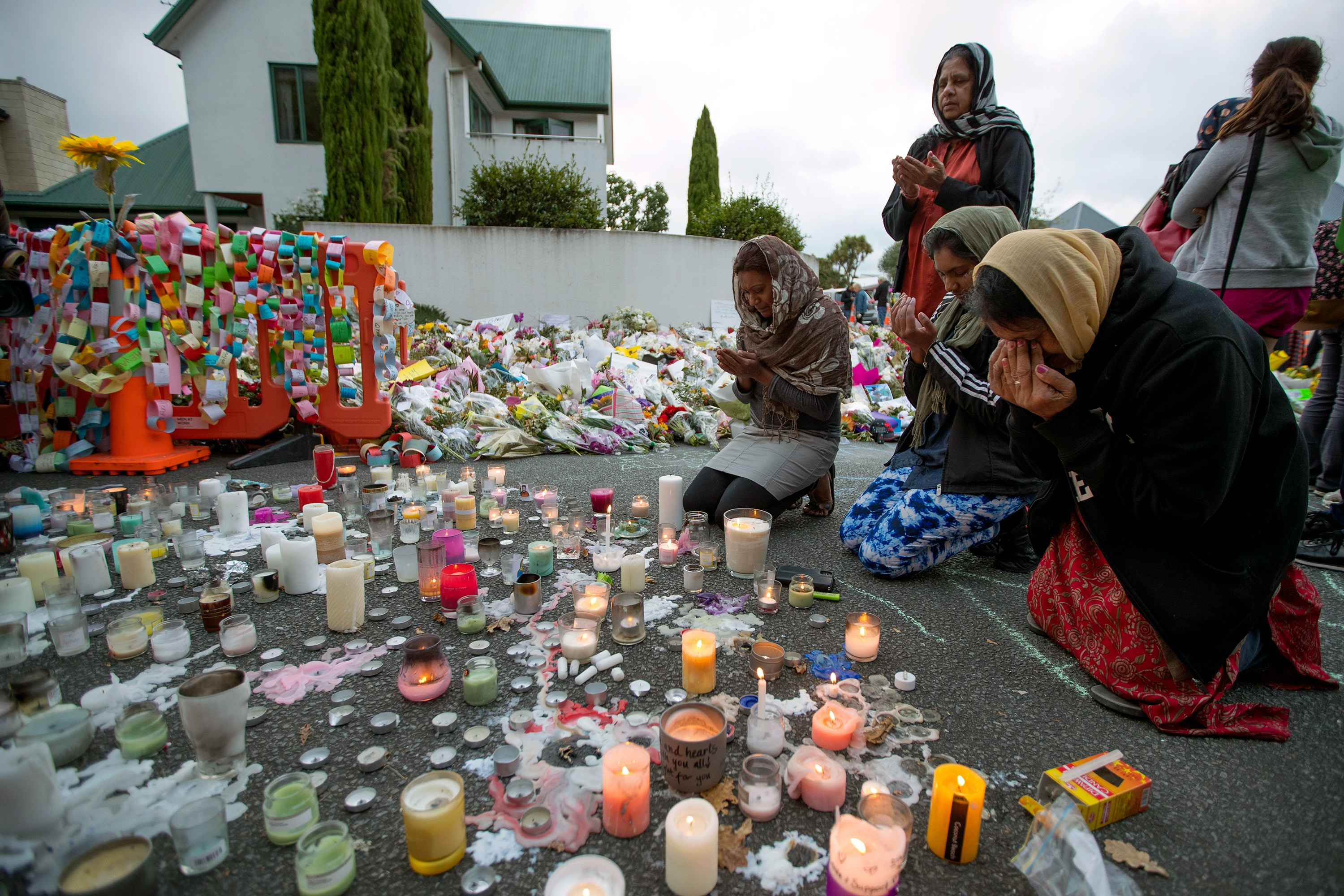 People mourn at a makeshift memorial site near the Al Noor mosque in Christchurch, New Zealand, Tuesday, March 19, 2019. Streets near the hospital that had been closed for four days reopened to traffic as relatives and friends of the victims of last week's mass shootings continued to stream in from around the world. (AP Photo/Vincent Thian)