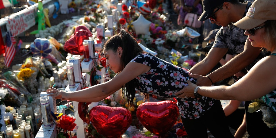 A woman leans over to write a message on a cross at a makeshift memorial at the scene of a mass shooting at a shopping complex, Tuesday, Aug. 6, 2019, in El Paso, Texas. (AP Photo/John Locher)