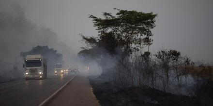 Caminhões dirigem ao lado de campos queimados na rodovia BR-163, no estado do Mato Grosso, em 23 de agosto de 2019.