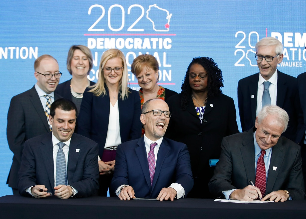 "Milwaukee Mayor Tom Barrett (bottom R) signs a document announcing the selection of Milwaukee as the 2020 Democratic National Convention host city as Wisconsin Governor Tony Evers (R) and Chair of the Democratic National Committee Tom Perez (bottom C) look on during a press conference at the Fiserv Forum in Milwaukee, Wisconsin on March 11, 2019. - Democrats have chosen Milwaukee as the site of their 2020 election convention, in an effort to win back swing voters in the American ""Rust Belt"" who helped elect Donald Trump. In announcing the decision, the Democratic Party emphasized it is the first time a Midwestern city other than Chicago has been chosen to host a party convention in more than 100 years. (Photo by Kamil Krzaczynski / AFP)        (Photo credit should read KAMIL KRZACZYNSKI/AFP/Getty Images)"