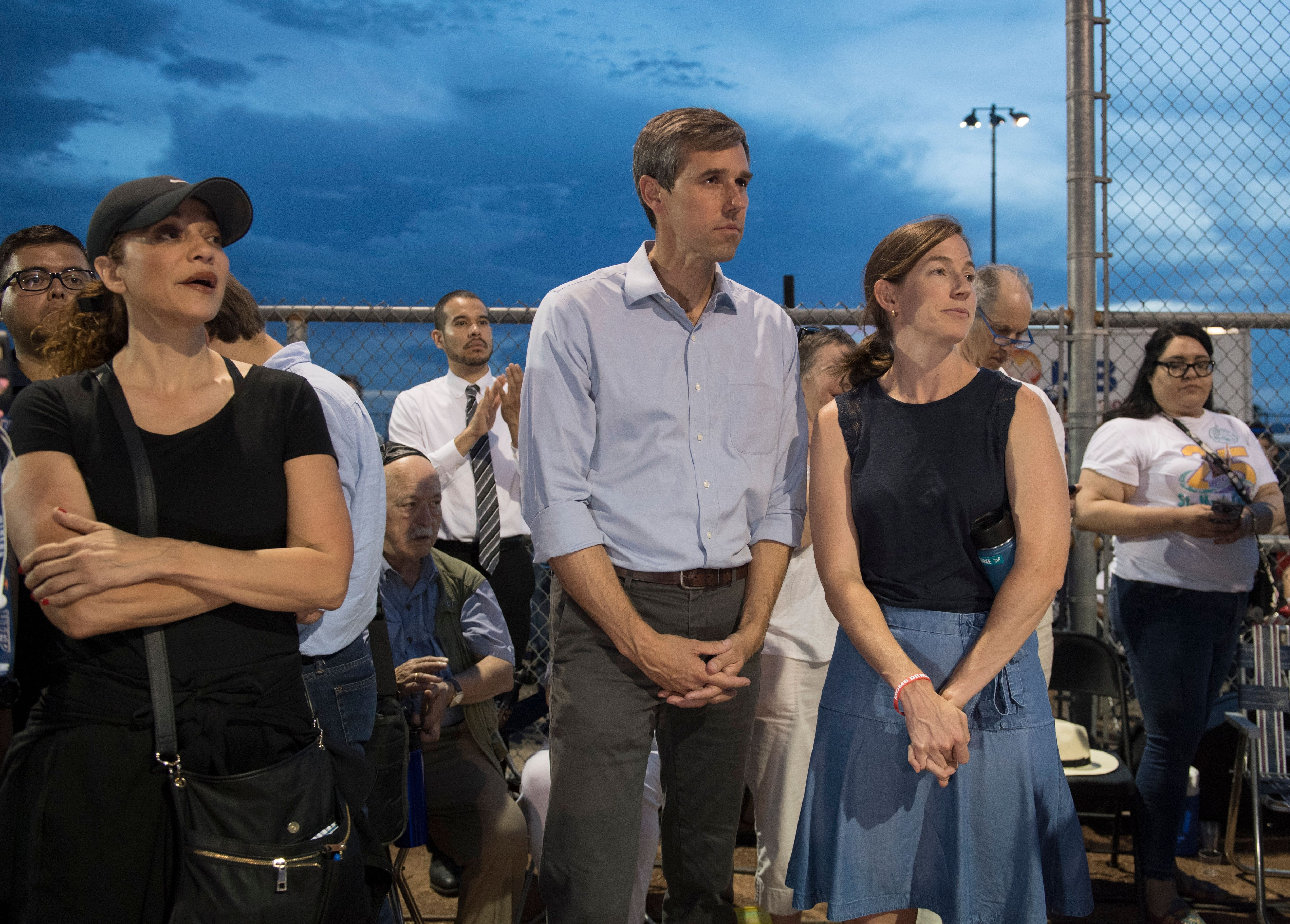 Democratic presidential hopeful and former US Representative for Texas' 16th congressional district Beto O'Rourke (C) waits to speak to the crowd, alongside his wife Amy Hoover Sanders (R), during a prayer and candle vigil organized by the city, after a shooting left 20 people dead at the Cielo Vista Mall WalMart in El Paso, Texas, on August 4, 2019.