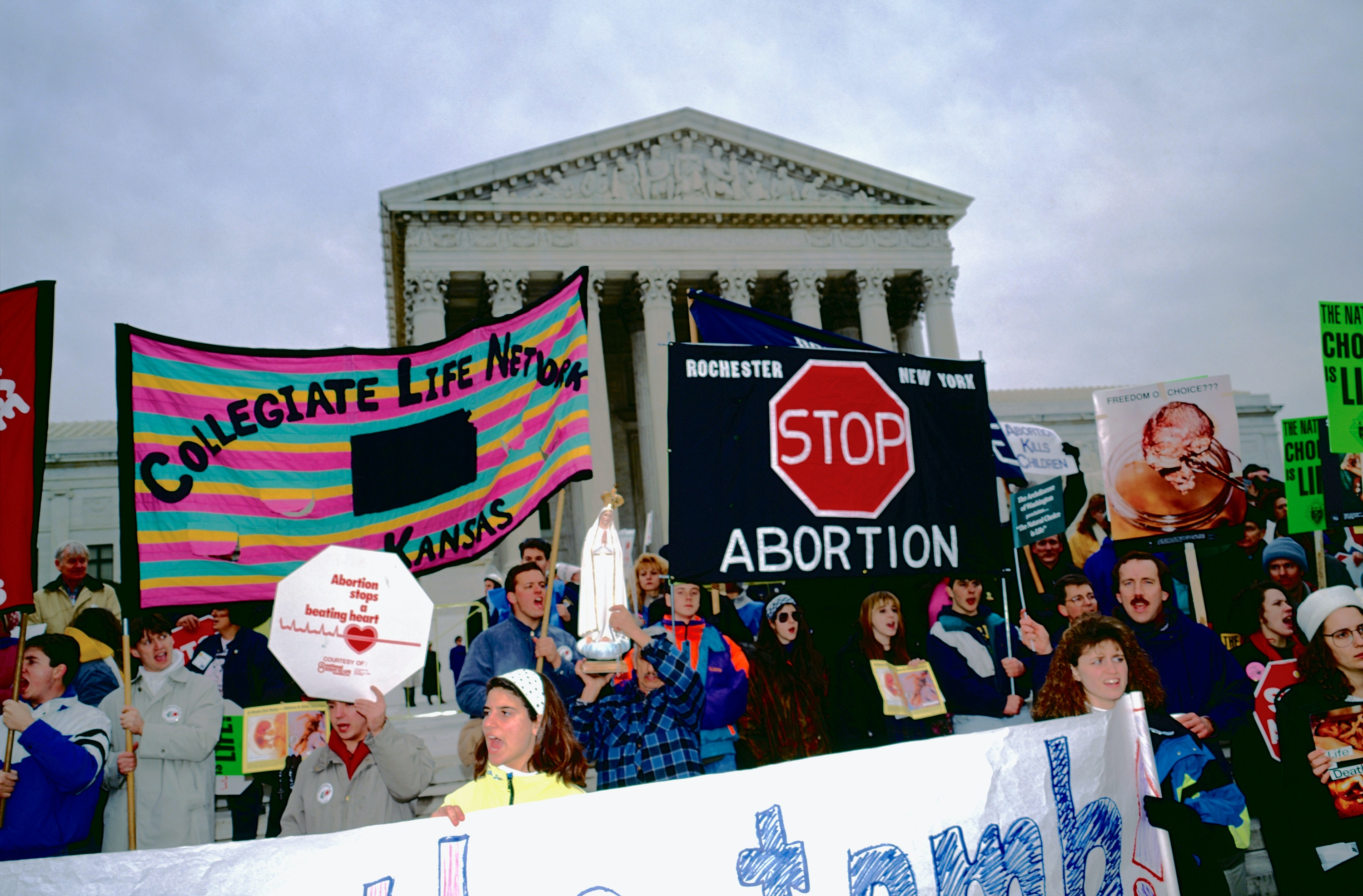 View of anti-abortion demonstrators, many with signs, in front of the US Supreme Court building during the annual March for Life, Washington DC, January 22, 1992. Among the signs are ones that read 'Collegiate Life Network, Kansas' and 'Stop Abortion.' (Photo by Mark Reinstein/Corbis via Getty Images)