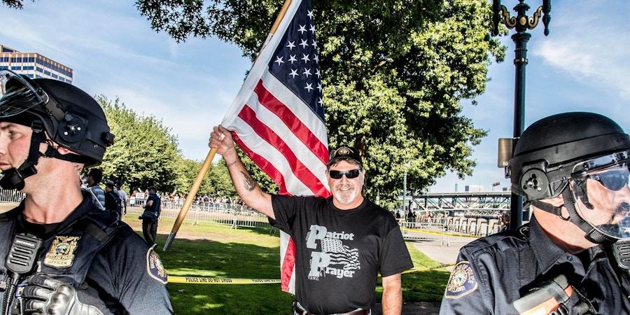 Policiais ao lado de um participante de uma manifestação pela liberdade de expressão organizada pelo grupo de extrema-direita Patriot Prayer em Portland, nos EUA, no dia 10 de setembro de 2017.