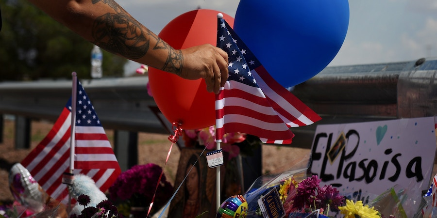 A man places an American flag in the pile of flowers that has gathered a day after a mass shooting at a Walmart store in El Paso, Texas, U.S. August 4, 2019.  REUTERS/Callaghan O'Hare     TPX IMAGES OF THE DAY - RC1E657255B0