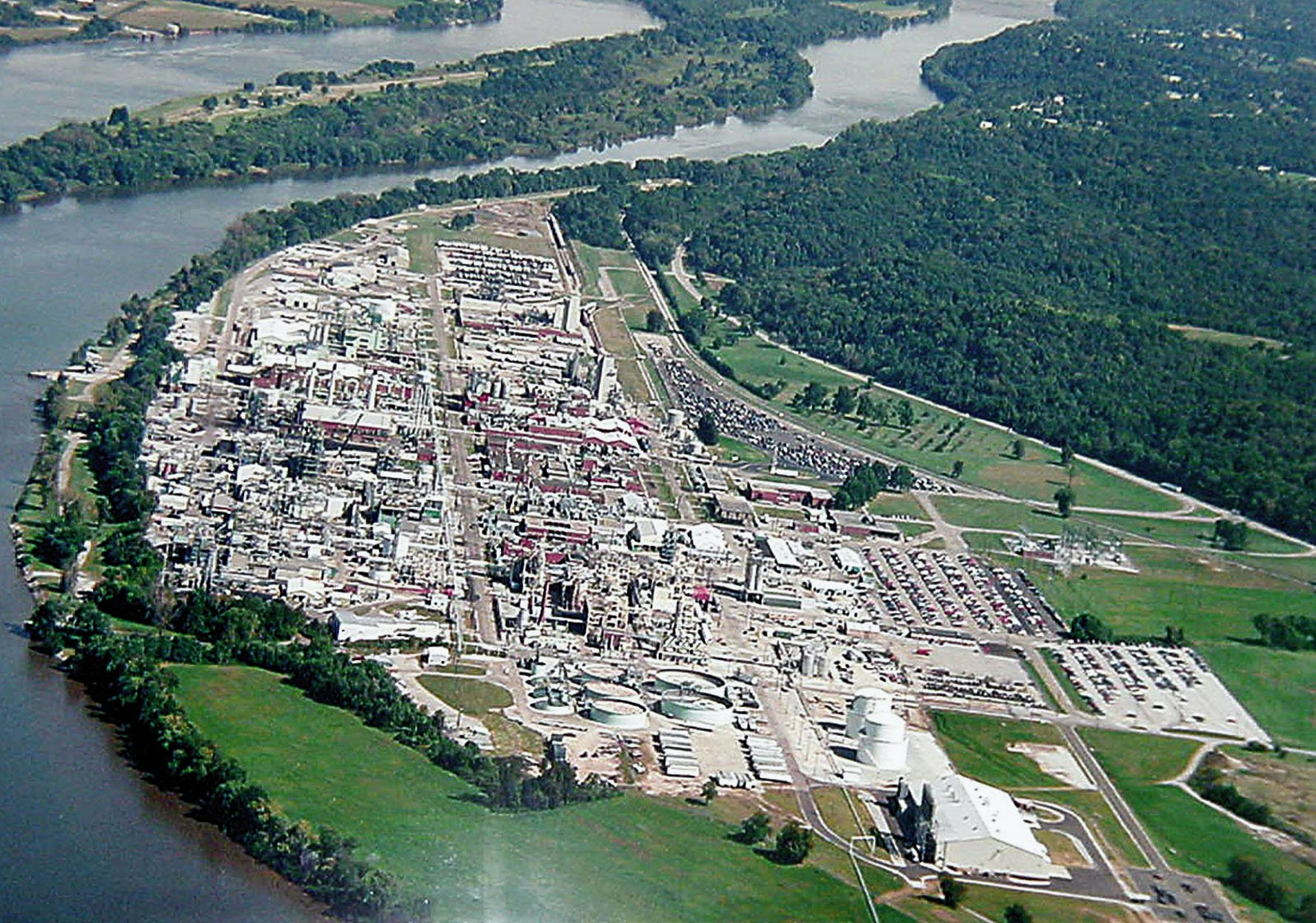 **FILE** DuPont Washington Works plant along Ohio River in Parkersburg, W. Va. is shown in this undated file photo. Up to 80,000 Ohio and West Virginia residents could be tested over the next year to determine if their health has been affected by drinking water containing a chemical used to make Teflon. DuPont Co. agreed in February to pay for the screenings to settle a class action lawsuit. (AP Photo/The Marietta Times)