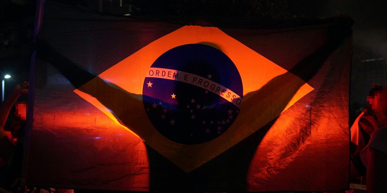 Um homem ostenta a bandeira nacional durante a comemoração da ida do então candidato a presidência Jair Bolsonaro ao segundo turno das eleições de 2018.