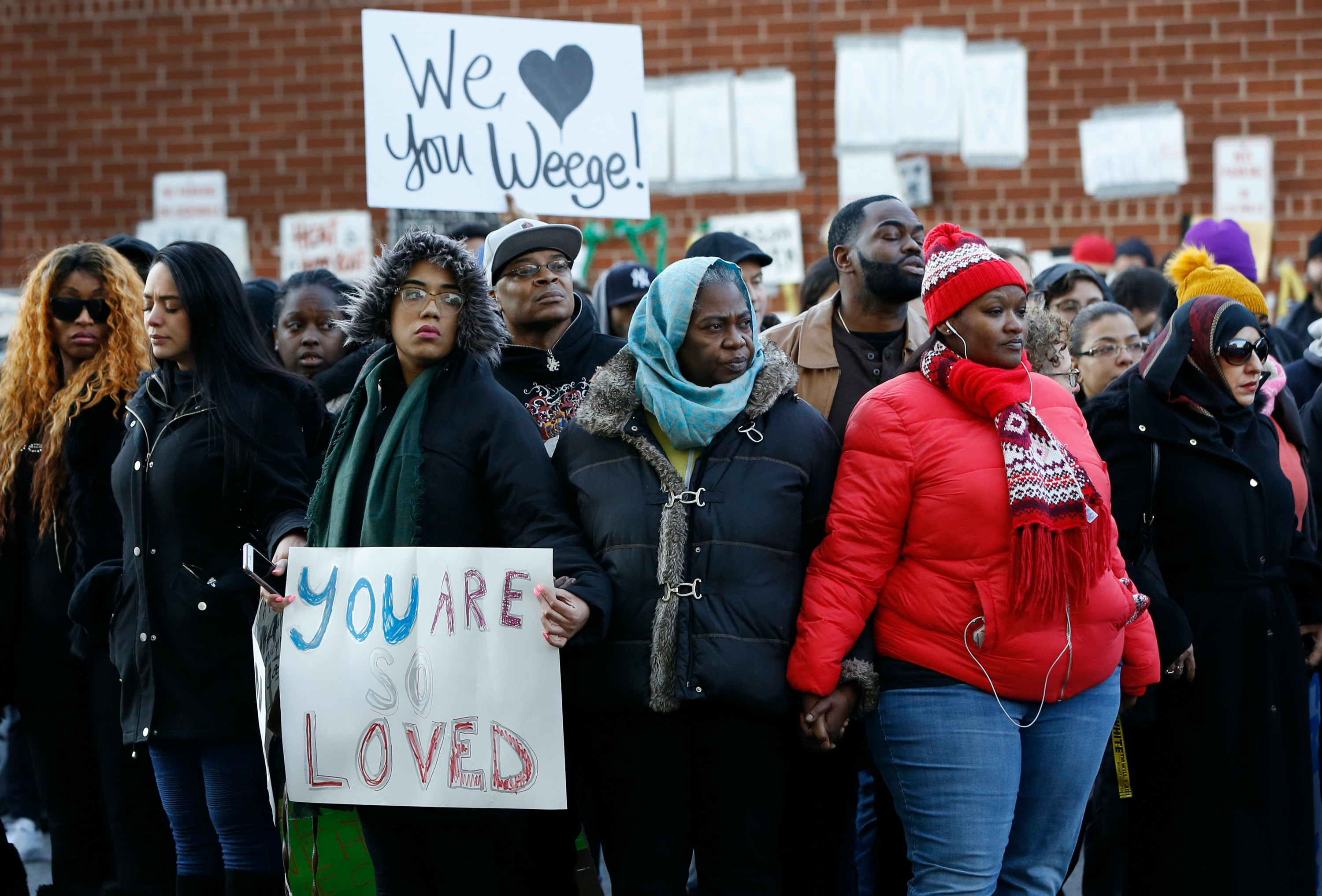 Protesters and family members of inmates hold hands while forming a prayer circle outside the Metropolitan Detention Center in New York on Sunday, Feb. 3, 2019. Some demonstrators protesting the lack of heat and electricity at the federal detention center in New York City attempted to enter the facility Sunday, and witnesses said guards drove them back with pushes, shoves and pepper spray. (AP Photo/Kathy Willens)