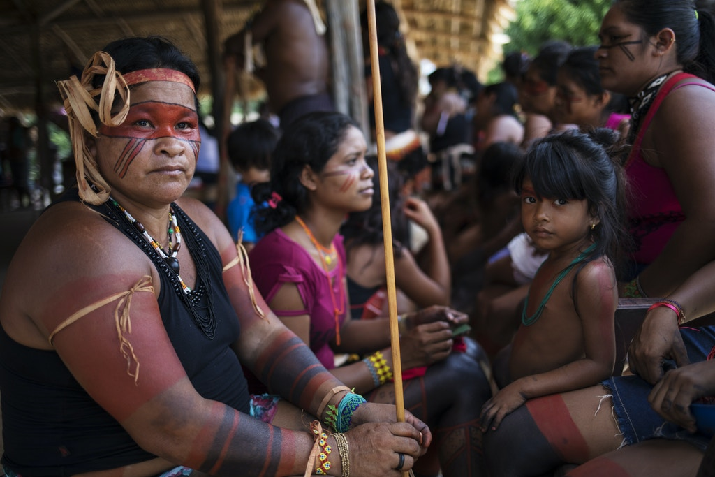 In this Sept. 3, 2019 photo, indigenous Tembé eomen listen to speakers during a meeting of tribes at the Tekohaw indigenous reserve, Para state, Brazil. President Jair Bolsonaro has argued that such large reserves have hindered Brazil's economic interests. But the indigenous people of Latin America's largest economy have everything at stake. (AP Photo/Rodrigo Abd)