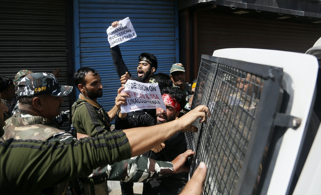 Indian policemen detain Kashmiri Shiite Muslims as they shout pro-freedom slogans after they made an attempt to take out a religious procession during restrictions in Srinagar, Indian controlled Kashmir, Sunday, Sept. 8, 2019. Authorities in Indian portion of Kashmiri imposed restrictions in some parts of Srinagar fearing religious processions marking the Muslim month of Muharram would turn into anti-India protests. (AP Photo/Mukhtar Khan)