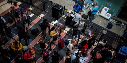 ARLINGTON, VA - MAY 24: Travelers wait in line to go through a security checkpoint at Ronald Reagan National Airport on May 24, 2019 in Arlington, Virginia. According to AAA, an additional 1.5 million Americans are expected to travel during the Memorial Day weekend, reaching near-record numbers.  (Photo by Zach Gibson/Getty Images)