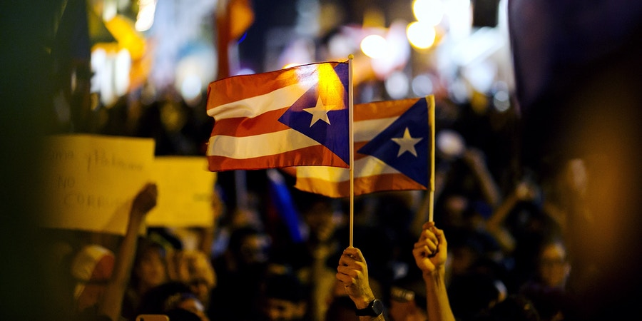 Demonstrators wave Puerto Rico flags as they gather during a protest demanding the resignation of Governor Ricardo Rossello in front of La Fortaleza in San Juan, Puerto Rico, on Wednesday, July 24, 2019. Rossello's looming resignation leaves Puerto Rico's government in shambles and may strengthen the hand of federal overseers tasked with imposing austerity on the bankrupt island to pull it from a years-long financial crisis. Photographer: Xavier Garcia/Bloomberg via Getty Images