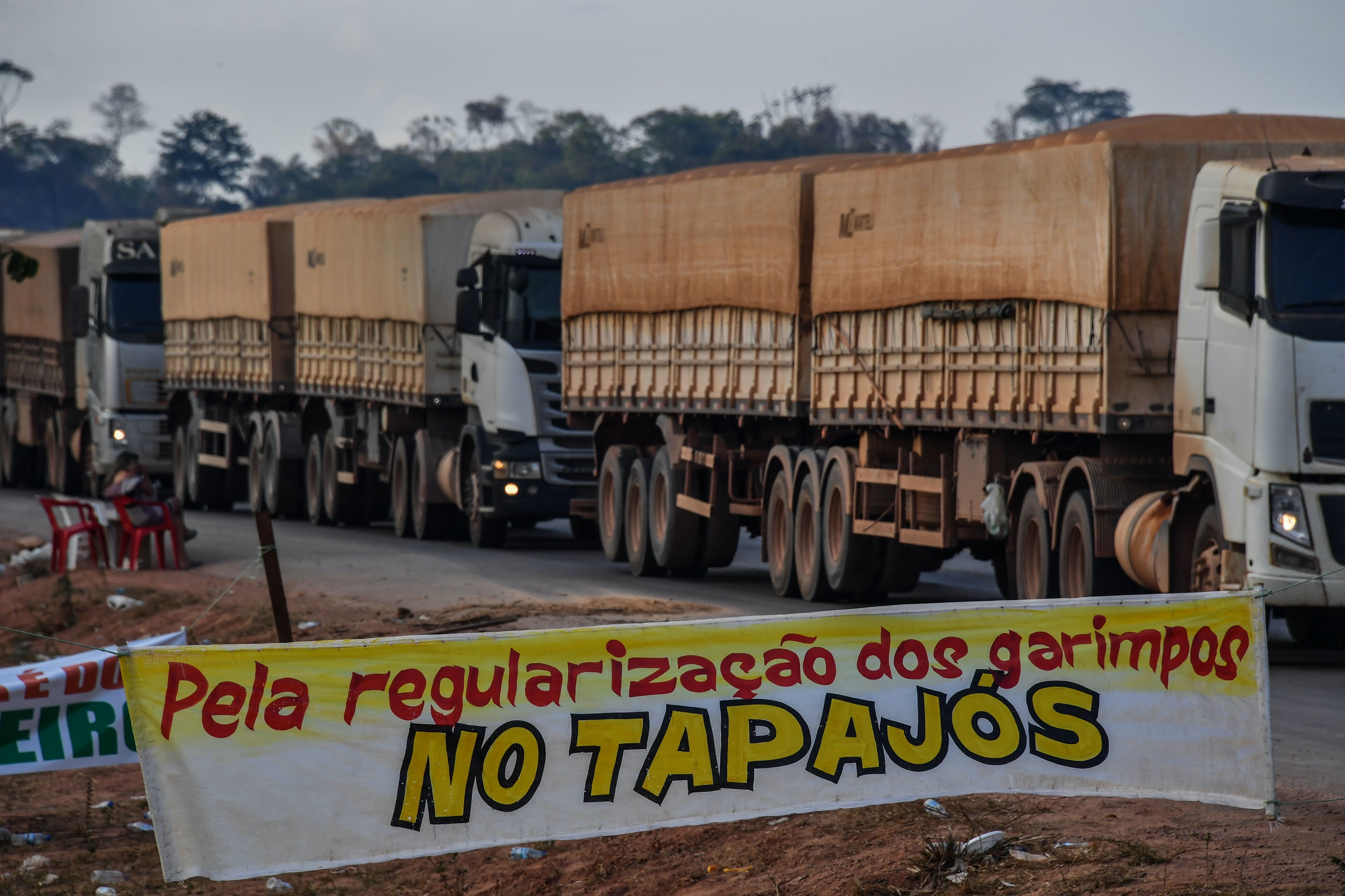 "Truckers line up behind a banner reading ""For the regularization of garimpos (illegal mines) in Tapajos"", referring to the Tapajos River, on the BR 163 highway, blocked by ""garimpeiros"" -illegal gold miners- during a protest in Morais Almeida, Itaituba, Para state, Brazil, on September 13, 2019. - Members of an indigenous tribe in the Amazon in northern Brazil on Friday called for wildcat miners to be allowed to prospect for gold on their land, saying it was a source of income. (Photo by NELSON ALMEIDA / AFP)        (Photo credit should read NELSON ALMEIDA/AFP/Getty Images)"