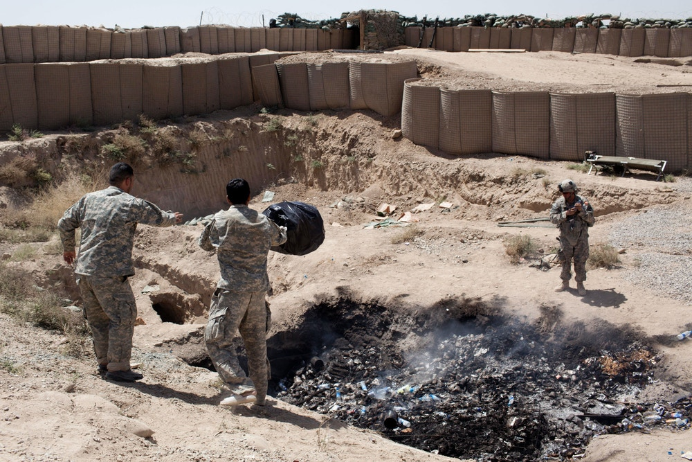 "ZHARI, AFGHANISTAN: Two interpreters for Bravo troop dump their trash in the base's ""burn pit."" Bravo ""Bonecrusher"" Troop of the 1-75 Cavalry, 101st Airborne Division recently deployed to the Pashmul area in the Zhari District of Kandahar Province which is a stronghold of the Taliban. They are partnered with Afghan soldiers from 2nd Company, 2nd Battalion, 3rd Brigade, 205th Corps. Bravo Troop is part of the new US surge into Kandahar, the birthplace of the Taliban. (Photo by Sebastian Meyer/Corbis via Getty Images)"