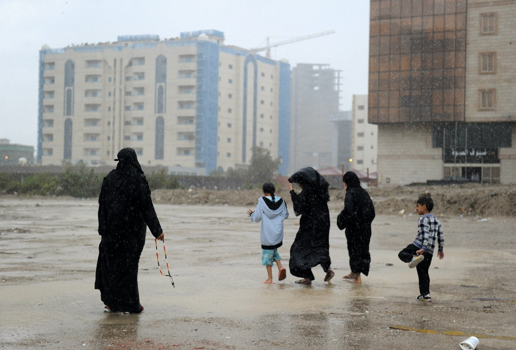 Saudi women and children stand in a flooded street in Jeddah on November 21, 2017.  Flash floods triggered by heavy rains swept through Jeddah, leaving motorists stranded and forcing authorities to shut schools and universities in Saudi Arabia's second biggest city. Dozens of people were plucked from vehicles engulfed by floodwaters, Saudi civil defence authorities said, with heavy rainfall expected to last at least until Wednesday.  / AFP PHOTO / Amer HILABI        (Photo credit should read AMER HILABI/AFP/Getty Images)