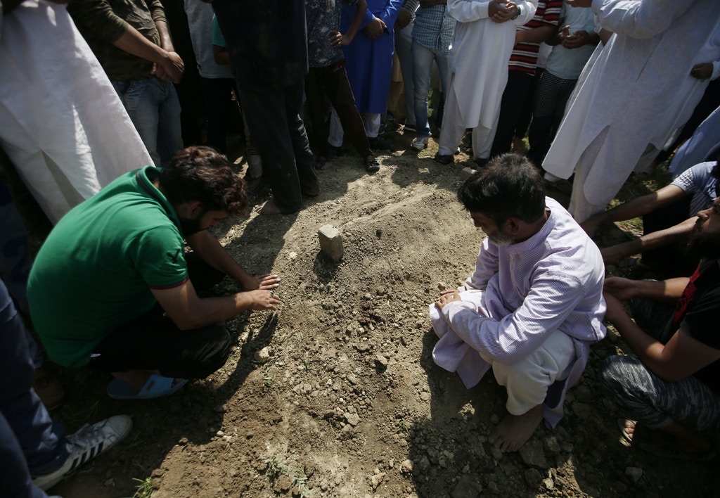 Relatives pray next to the grave of Asrar Ahmed Khan, who died on Tuesday night after succumbing to wounds during a protest on August 6, in Srinagar, September 4, 2019. REUTERS/Danish Ismail - RC1E20AEEAB0