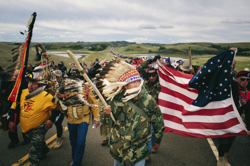 Catcher Cuts The Road, an Iraq War veteran, leads a protest march to a sacred burial ground at the Standing Rock Indian Reservation in North Dakota, Sept. 9, 2016. A federal judge on Friday denied the Standing Rock Sioux Tribe's efforts to halt the construction of a pipeline skirting the northern edge of the reservation on Friday; on the same day, the government ordered a the pipeline company to pause its work. (Alyssa Schukar/The New York Times)
