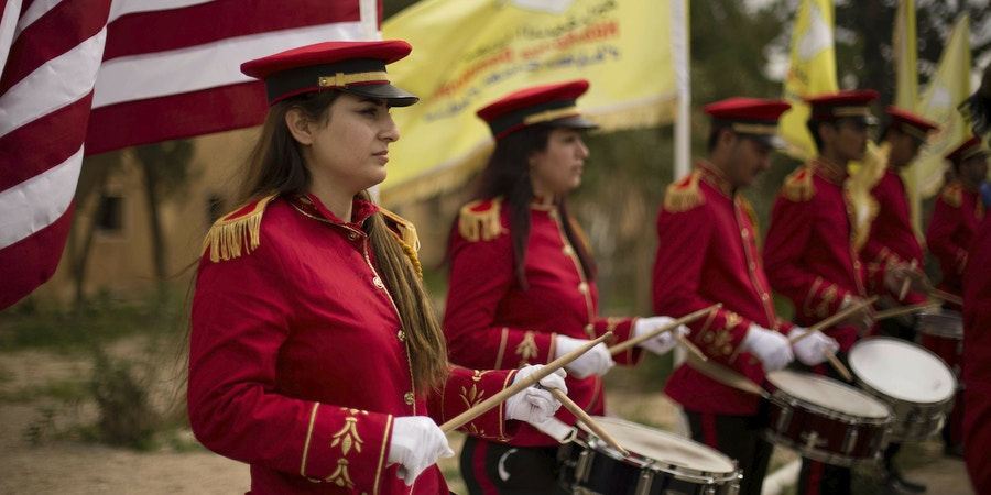 A military band performs ahead of a ceremony at al-Omar Oil Field marking the U.S.-backed Syrian Democratic Forces (SDF) capture of Baghouz, Syria, after months of fighting to oust Islamic State militants Saturday, March 23, 2019.  The elimination of the last Islamic State stronghold in Baghouz brings to a close a grueling final battle that stretched across several weeks and saw thousands of people flee the territory and surrender in desperation, and hundreds killed. (AP Photo/Maya Alleruzzo)