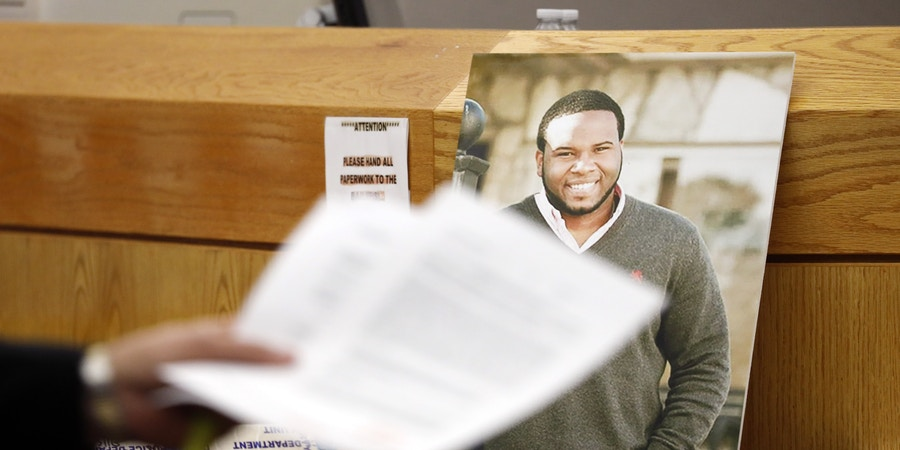 A photo of victim Botham Jean leans against Judge Tammy Kemp's bench during the murder trial of former Dallas police officer Amber Guyger, Tuesday, Sept. 24, 2019, in Dallas. Guyger is accused of shooting Jean, her unarmed black neighbor, in his Dallas apartment.  (Tom Fox/The Dallas Morning News via AP, Pool)
