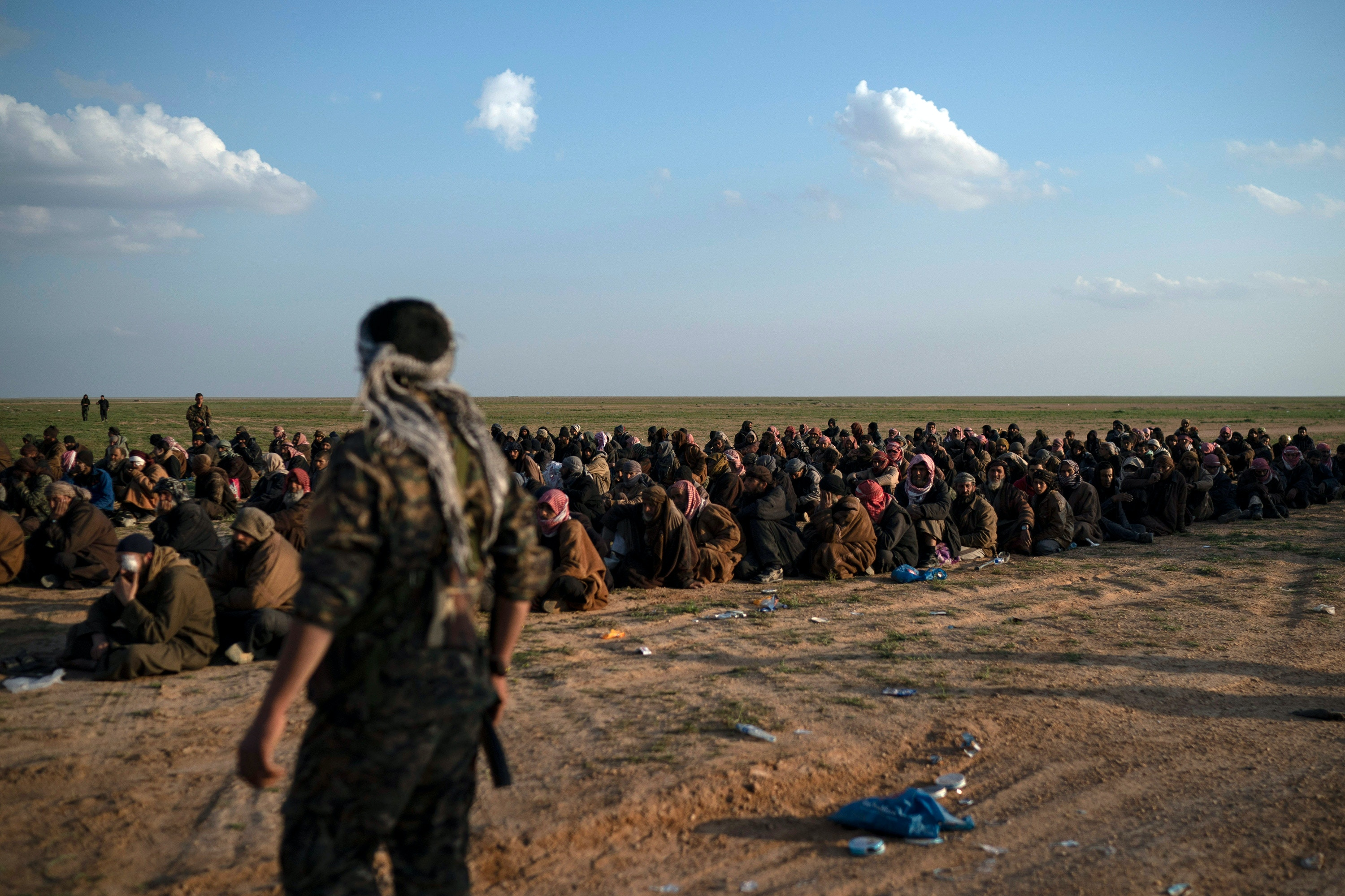 FILE - In this Feb. 22, 2019 file photo, U.S.-backed Syrian Democratic Forces (SDF) fighters stand guard next to men waiting to be screened after being evacuated out of the last territory held by Islamic State group militants, near Baghouz, eastern Syria. The IS could get a new injection of life if conflict erupts between the Kurds and Turkey in northeast Syria as the U.S. pulls its troops back from the area. The White House has said Turkey will take over responsibility for the thousands of IS fighters captured during the long campaign that defeated the militants in Syria. But it's not clear how that could happen. (AP Photo/Felipe Dana, File)