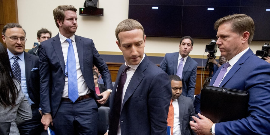 Facebook CEO Mark Zuckerberg, center, accompanied by Facebook vice president for U.S. public policy, Kevin Martin, right, takes a break from testimony before a House Financial Services Committee hearing on Capitol Hill in Washington, Wednesday, Oct. 23, 2019, on Facebook's impact on the financial services and housing sectors. (AP Photo/Andrew Harnik)