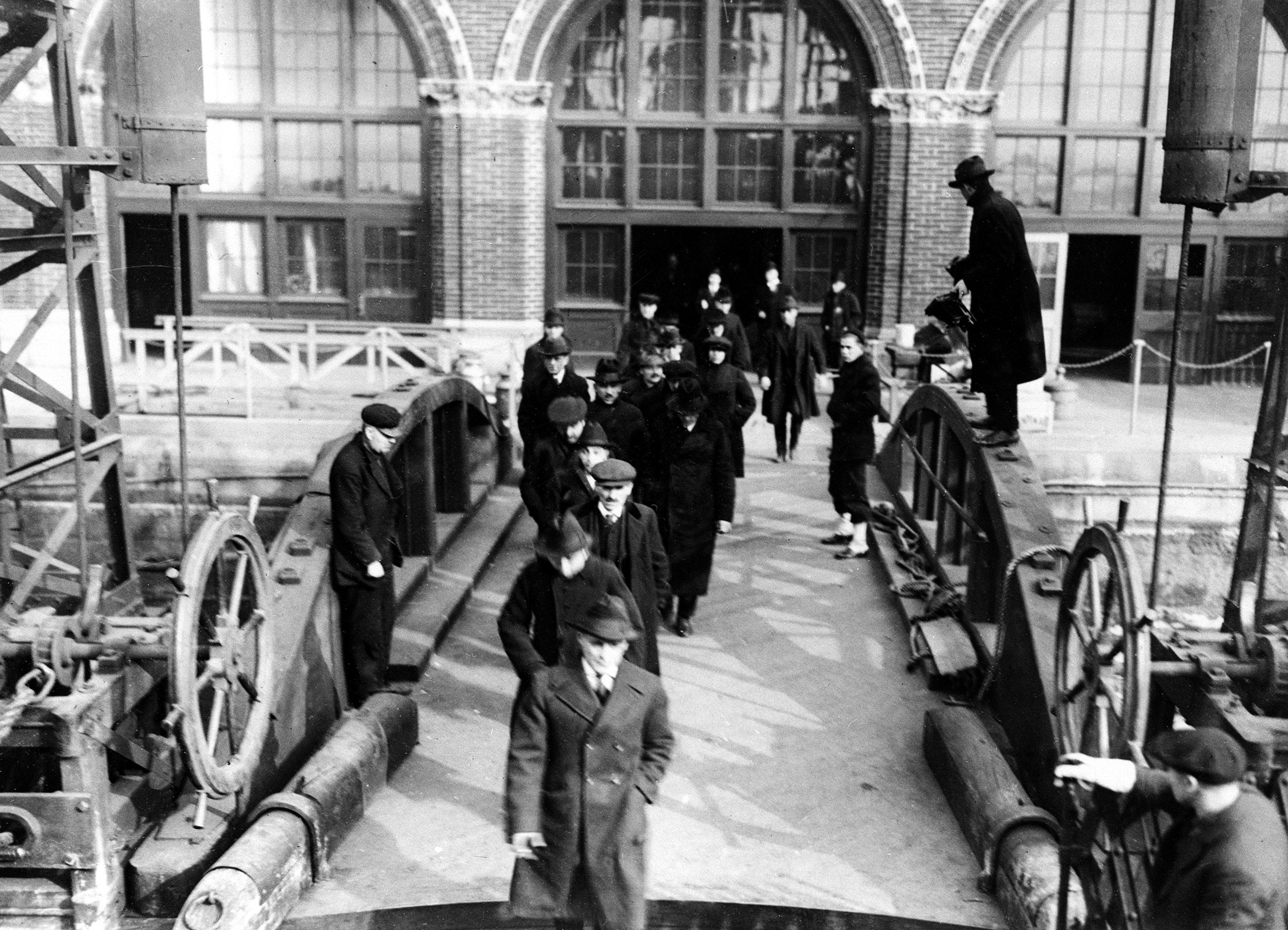 People who have been arrested in the federal drive against radicals are shown as they arrive at Ellis Island, in New York City, on April 7, 1920. Deportation hearings are held on the island to determine whether they are to stay in the United States. (AP Photo)