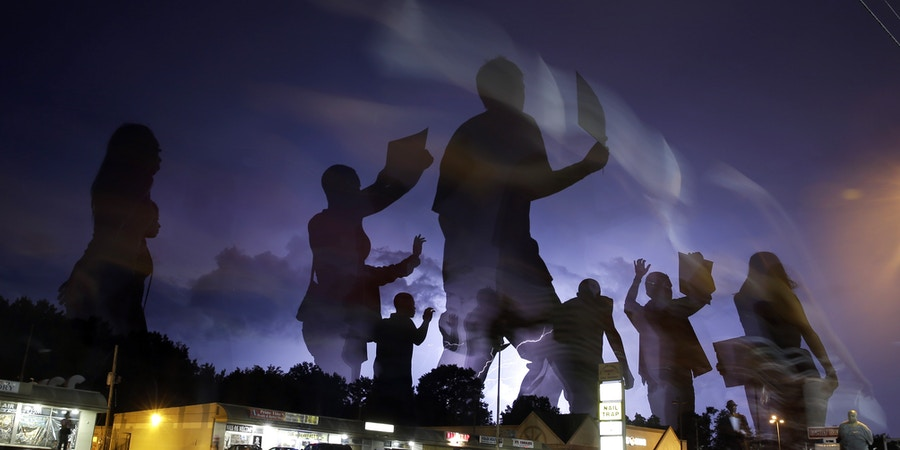 FILE - In this Aug. 20, 2014 file photo taken with a long exposure, protesters march in the street as lightning flashes in the distance in Ferguson, Mo. The one year anniversary of the shooting of Michael Brown, which sparked months of nationwide protests and launched the