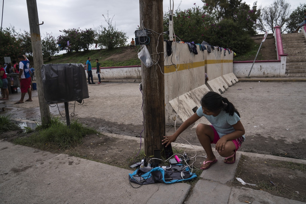 Nathaly, 9, who is seeking asylum with her mother, charges her tablet in an encampment where they live near the Gateway International Bridge on Oct. 22, 2019 in Matamoros, Mexico. Verónica G. Cárdenas for The Intercept