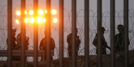 TIJUANA, MEXICO - NOVEMBER 26:  U.S. Border Patrol agents stand watch on the U.S. side of the U.S.-Mexico border fence at dusk on November 26, 2018 in Tijuana, Mexico. Customs and Border Protection agents controversially deployed tear gas during an incident where migrants attempted to rush the border November 25 in Tijuana. Around 6,000 migrants from Central America have arrived in the city with the mayor of Tijuana declaring the situation a 'humanitarian crisis'.  (Photo by Mario Tama/Getty Images)