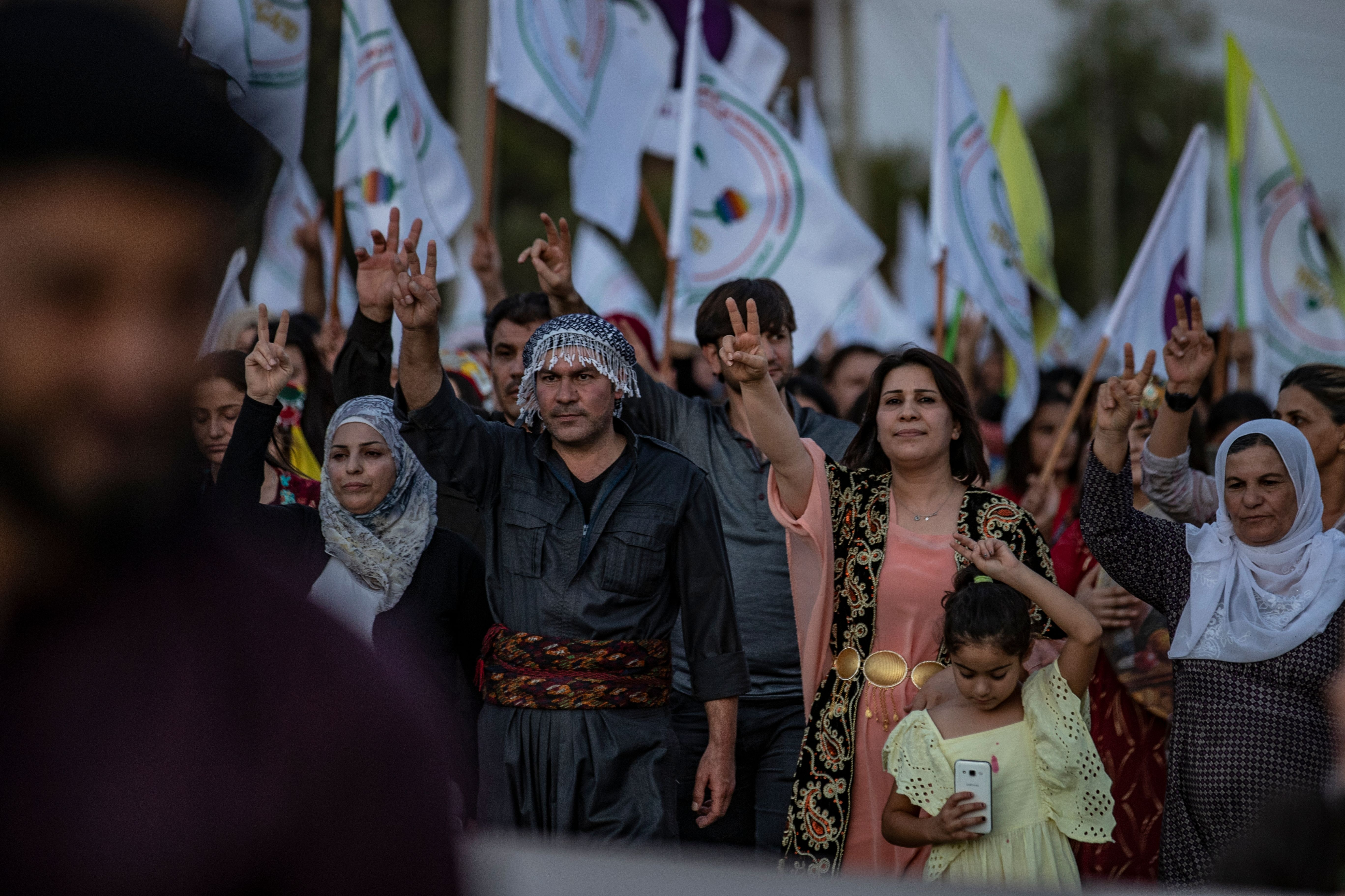 Syrian Kurdish demonstrators flash the V for victory sign as they march in the northeastern city of Qamishli on August 27, 2019 during a protest against Turkish threats to invade the Kurdish region. - The Kurdish authorities in northeast Syria said Tuesday their forces had started to withdraw from outposts along the Turkish border after a US-Turkish deal for a buffer zone there. (Photo by Delil SOULEIMAN / AFP)