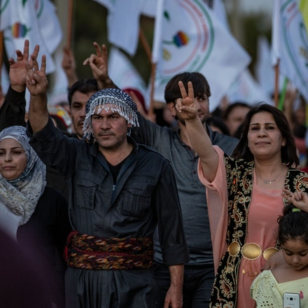 Syrian Kurdish demonstrators flash the V for victory sign as they march in the northeastern city of Qamishli on August 27, 2019 during a protest against Turkish threats to invade the Kurdish region. - The Kurdish authorities in northeast Syria said Tuesday their forces had started to withdraw from outposts along the Turkish border after a US-Turkish deal for a buffer zone there. (Photo by Delil SOULEIMAN / AFP) (Photo credit should read DELIL SOULEIMAN/AFP/Getty Images)