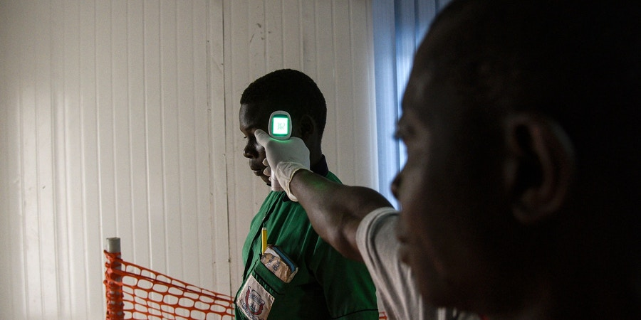 A health official checks the temperature of a school going pupil from the Democratic Republic of Congo (DRC) at the Mpondwe border point, separating Uganda and the DRC, as he walks through the computerised Mpondwe Health Screening Facility on August 14, 2019. - Every day at dawn, Doneka Kabowo, a Congolese teenager, walks miles into the jungle, with the threat of armed militiamen who roam the area, to go to school across the border in Uganda. But for some time now, another obstacle has developed for the 15-year-old and hundreds of schoolchildren who daily travel from the Democratic Republic of Congo (DRC) to Uganda to study: health checks for prevent the transmission of the Ebola virus. (Photo by ISAAC KASAMANI / AFP)        (Photo credit should read ISAAC KASAMANI/AFP/Getty Images)