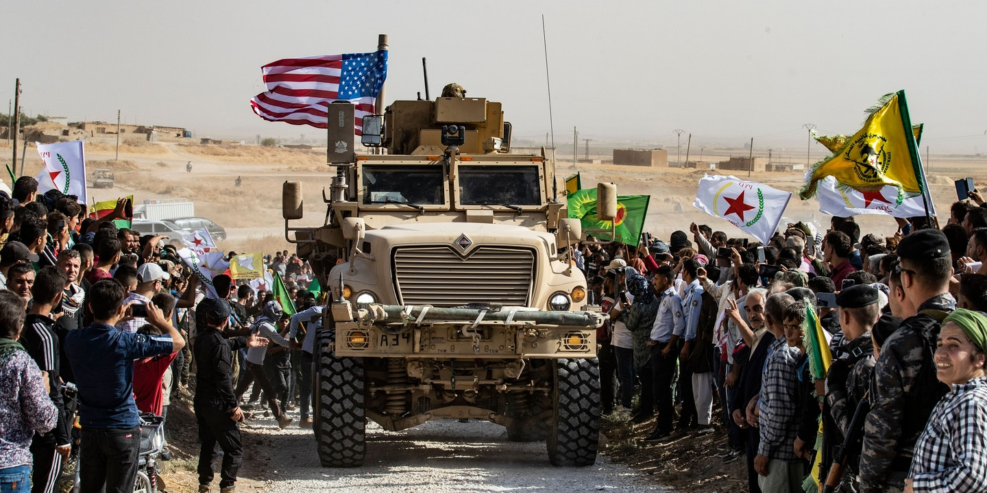 "Syrian Kurds gather around a US armoured vehicle during a demonstration against Turkish threats next to a US-led international coalition base on the outskirts of Ras al-Ain town in Syria's Hasakeh province near the Turkish border on October 6, 2019. - Ankara had reiterated on October 5 an oft-repeated threat to launch an ""air and ground"" operation in Syria against a Kurdish militia it deems a terrorist group. (Photo by Delil SOULEIMAN / AFP) (Photo by DELIL SOULEIMAN/AFP via Getty Images)"