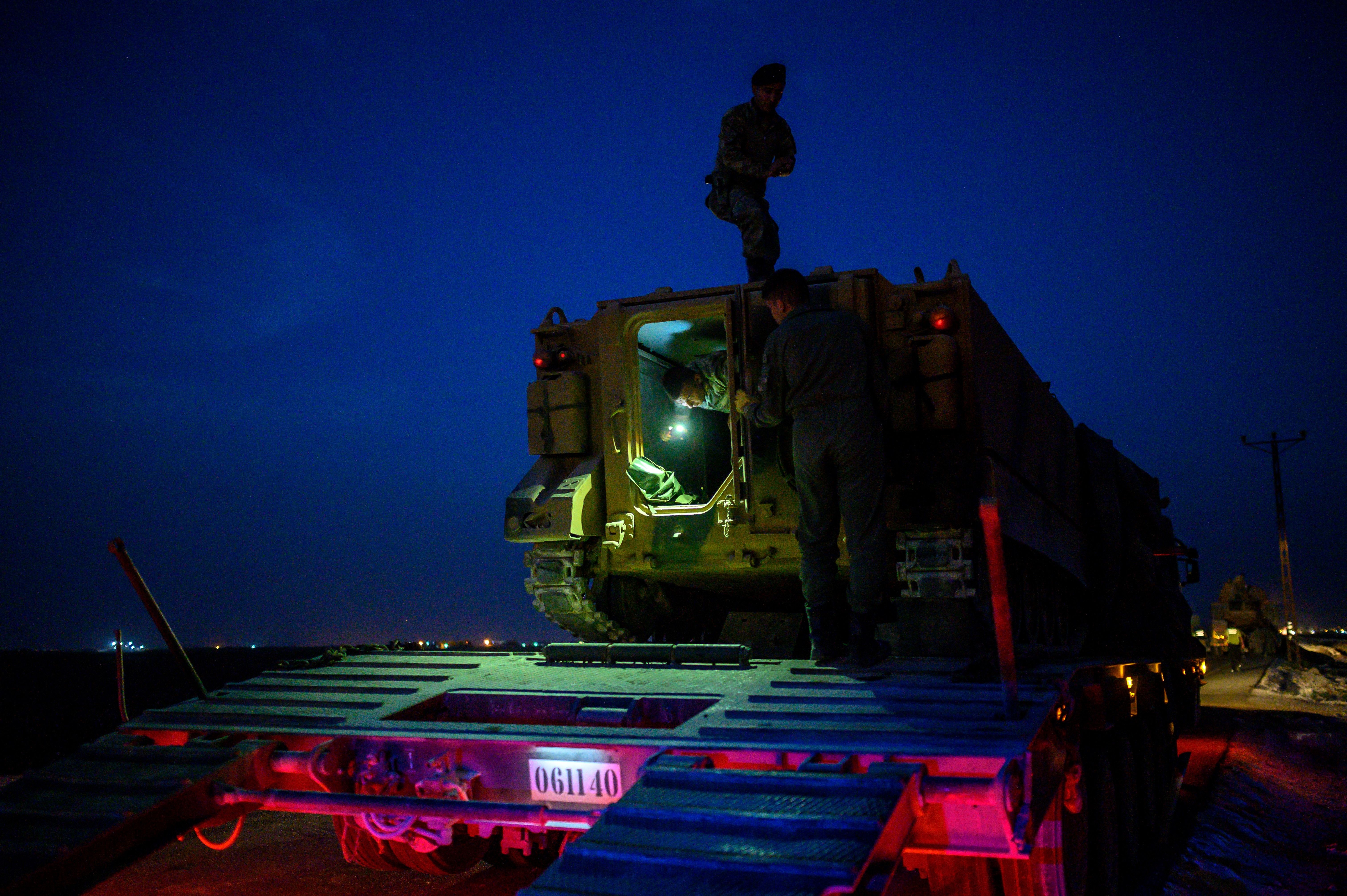 "Turkish soldiers prepare an armored vehicle as Turkish armed forces drive towards the border with Syria near Akcakale in Sanliurfa province on October 8, 2019. - Turkey said on October 8, 2019, it was ready for an offensive into northern Syria, while President Donald Trump insisted the United States had not abandoned its Kurdish allies who would be targeted in the assault. Trump has blown hot and cold since a surprise announcement two days before that Washington was pulling back 50 to 100 ""special operators"" from Syria's northern frontier. (Photo by BULENT KILIC / AFP) (Photo by BULENT KILIC/AFP via Getty Images)"