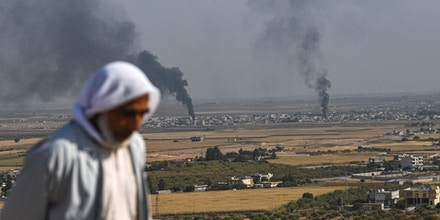 A man looks on as smoke rises from the Syrian town of Ras al-Ain, in a picture taken from the Turkish side of the border in Ceylanpinar on October 11, 2019, on the third day of Turkey's military operation against Kurdish forces. - Turkey will not stop its operation against Kurdish militants in northern Syria, President Recep Tayyip Erdogan said Friday, dismissing what he called