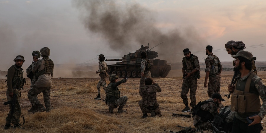 Turkish soldiers and Turkey-backed Syrian fighters gather on the northern outskirts of the Syrian city of Manbij near the Turkish border on October 14, 2019, as Turkey and its allies continue their assault on Kurdish-held border towns in northeastern Syria. - Turkey wants to create a roughly 30-kilometre (20-mile) buffer zone along its border to keep Kurdish forces at bay and also to send back some of the 3.6 million Syrian refugees it hosts. (Photo by Zein Al RIFAI / AFP) (Photo by ZEIN AL RIFAI/AFP via Getty Images)