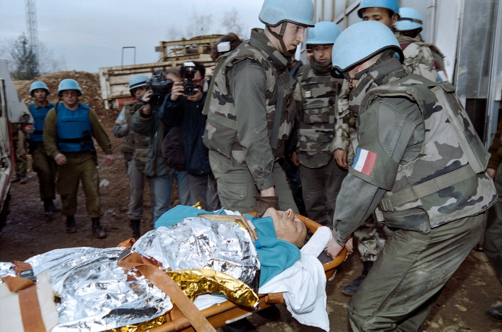 UN personnel carry one of the victim of the Markale market place attack in Sarajevo at Sarajevo airport on February 06, 1994, to be flown out to American hospitals near Frankfurt or Zagreb. The day before a bomb exploded at main Sarajevos marketplace, killing 68 people and wounding 200.        (Photo credit should read PASCAL GUYOT/AFP/Getty Images)