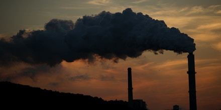 Emissions rise from the Northern Indiana Public Service Co. (NIPSCO) Bailly generating station on the shore of Lake Michigan at dusk in Chesterton, Indiana, U.S., on Wednesday, Oct. 7, 2015. For the second month in a row, natural gas beat coal as the main source of U.S. electricity generation, accounting for 35.2 percent of supplies in August, a government report showed. Photographer: Luke Sharrett/Bloomberg via Getty Images
