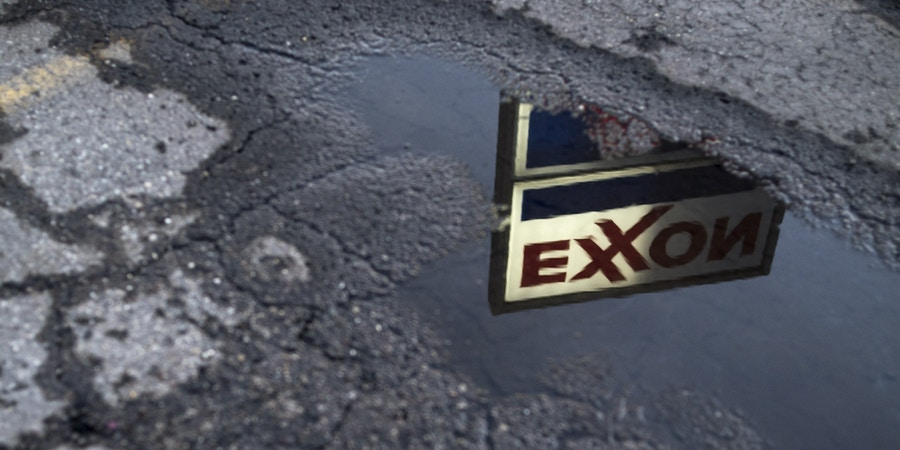 Exxon Mobil Corp. signage is reflected in a puddle at a gas station in Nashport, Ohio, U.S., on Friday, Jan. 26, 2018. Exxon Mobil Corp. is scheduled to release earnings figures on February 2. Photographer: Ty Wright/Bloomberg via Getty Images