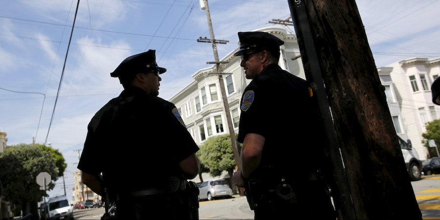 San Francisco police officers stand on Lombard Street, a popular tourist spot also known as the