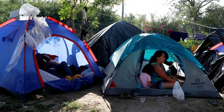 Central American migrants are seen inside their tents in an encampment in Matamoros, Mexico, at the end of the Gateway International Bridge, where migrants sent back under the