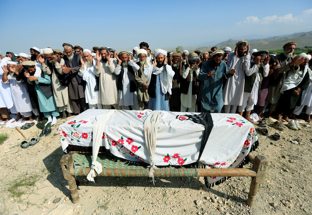 Relatives and residents pray near a coffin during a funeral ceremony of one of the victims after a drone strike, in Khogyani district of Nangarhar province, Afghanistan September 19, 2019.REUTERS/Parwiz - RC1790411250