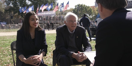 Rep. Alexandria Ocasio-Cortez, left, and Sen. Bernie Sanders, center, speak with The Intercept's Ryan Grim, right, at a campaign rally at Queensbridge Park in New York City, on Oct. 19, 2019.