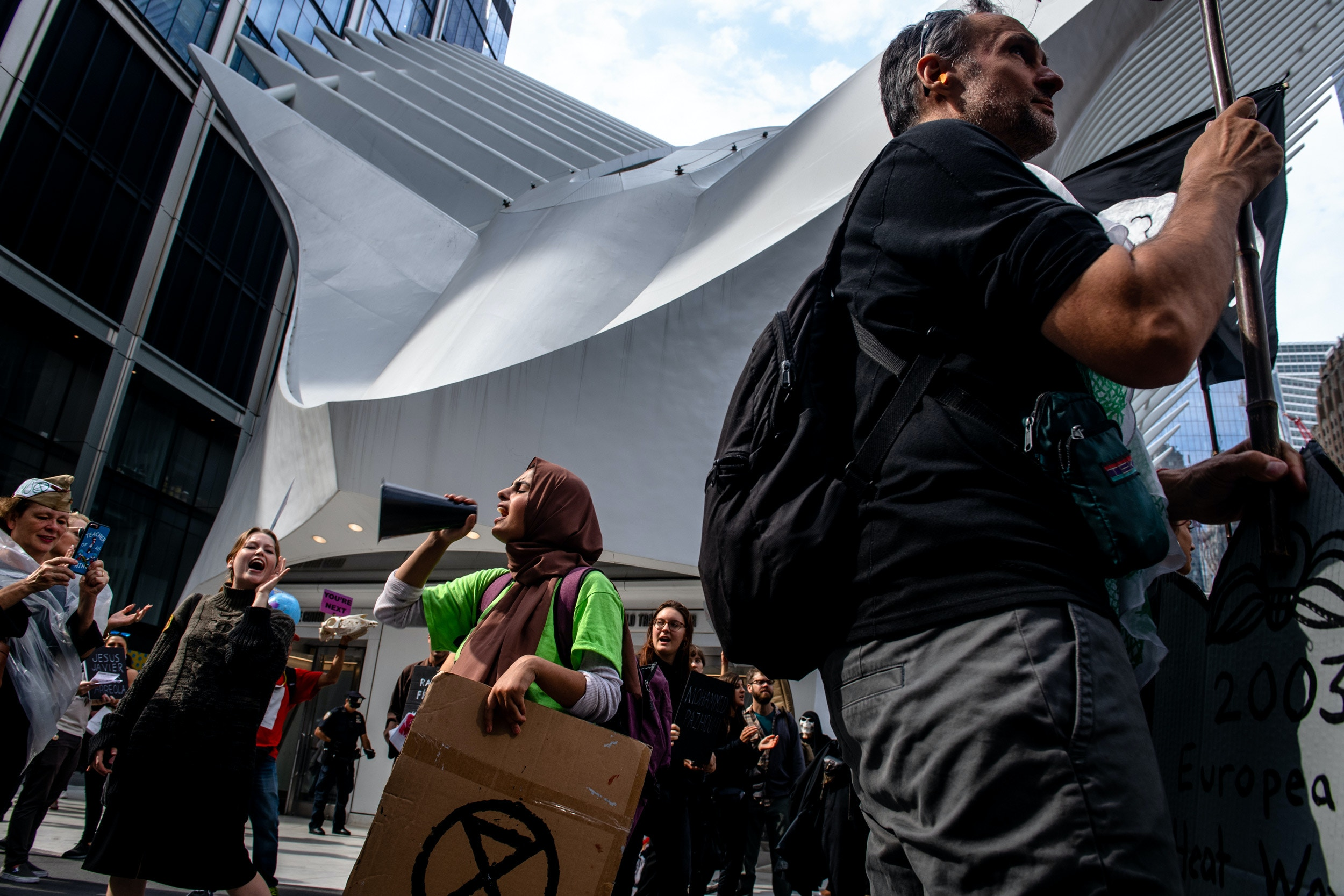 "NEW YORK, NEW YORK– OCTOBER 7, 2019: Ayisha S., 20, leads a group of Extinction Rebellion members (commonly referred to as XR) toward the Oculus after staging a ""die-in"" on the street in mid-day traffic."