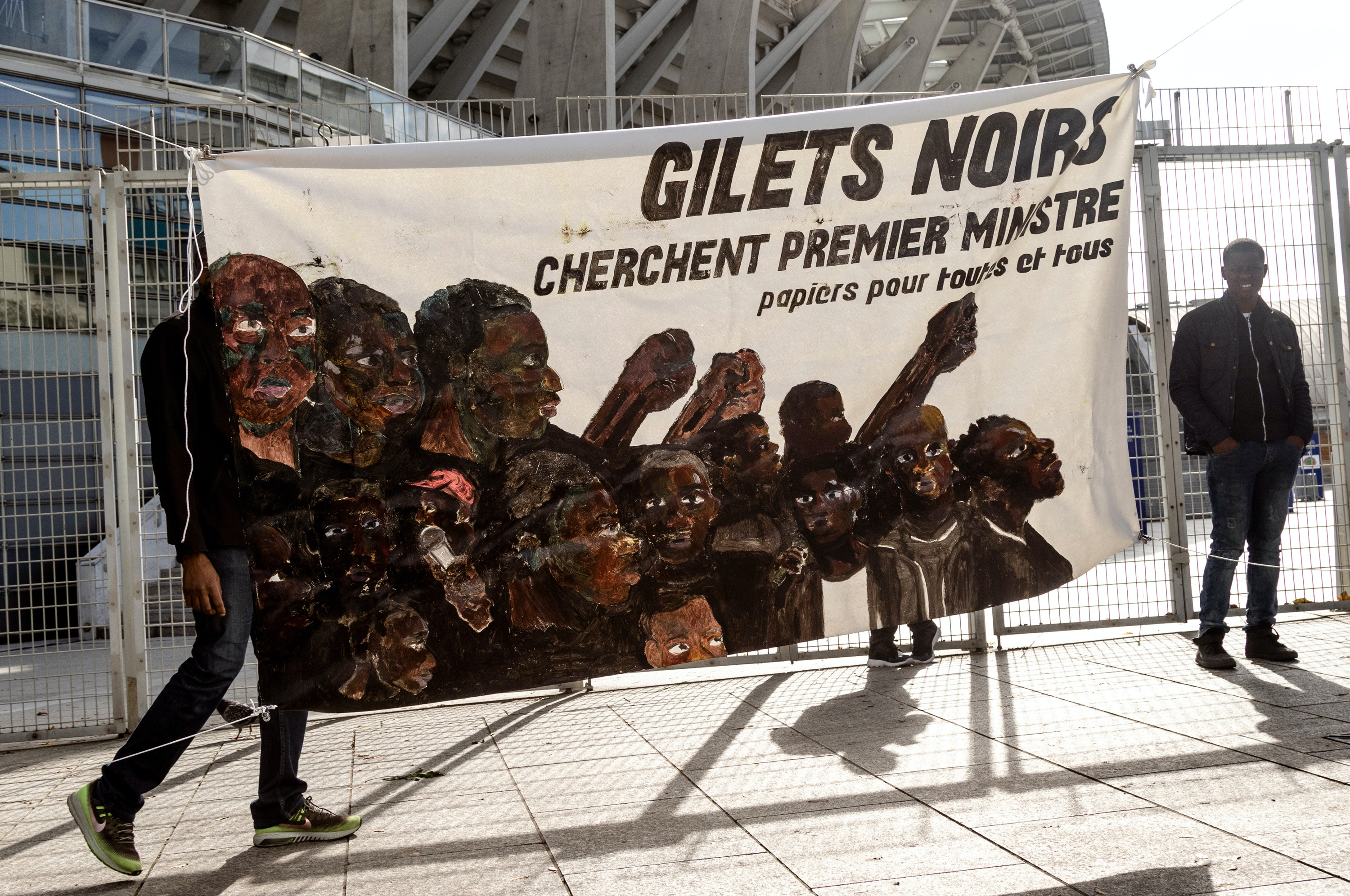 "A banner reads, ""Black Vests seeking the Prime Minister. Papers for everyone."" at the Gilet Noirs protest outside of Charlety Stadium. The neutral meeting place where negotiations with Elior, a catering company that employs undocumented migrants, were discussed, Friday, Oct. 11, 2019. (Emma Francis/The Intercept)"