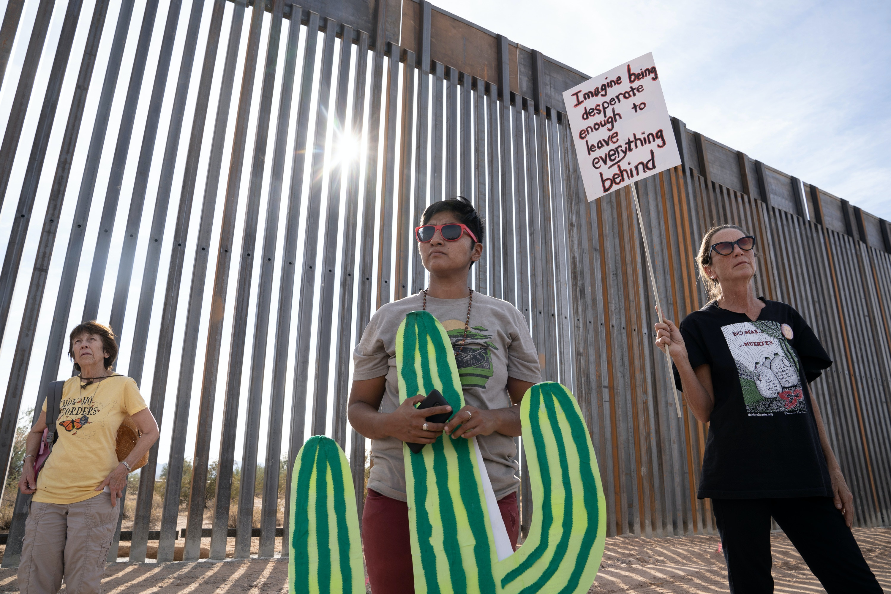 Amber Ortega, 33, (center), a Hia-Ced O'odham and Tohono O'odham activist, student and spoken word poet, and Mary Diamond (right) stand in front of the newly constructed U.S. - Mexico border wall in the Organ Pipe Cactus National Monument on November 9, 2019 during a day of actions protesting the building of the wall. The area is sacred to the Hia-Ced O'odham and the Tohono O'odham nations.Photo by Kitra Cahana/MAPS for The Intercept
