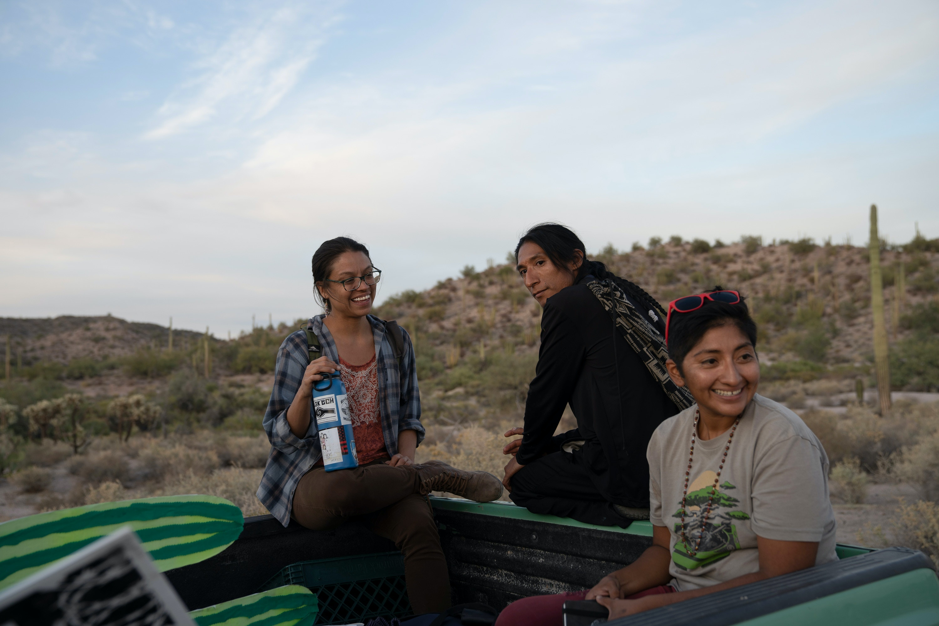 Amber Ortega, 33, (left), a Hia-Ced O'odham and Tohono O'odham activist, student and spoken word poet, Victor Garcia (center), a Hia-Ced O'odham and Tohono O'odham activist and Nellie Jo David, 36 (right), a Hia-Ced O'odham and Tohono O'odham activist sit in the back of a pick-up truck after protesting by the newly constructed U.S. - Mexico border wall in the Organ Pipe Cactus National Monument on November 9, 2019 during a day of actions protesting the building of the wall. The area is sacred to the Hia-Ced O'odham and the Tohono O'odham nations.  Photo by Kitra Cahana/MAPS for The Intercept