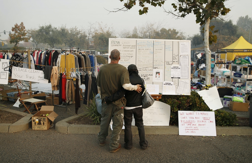 Tera Hickerson, right, and Columbus Holt embrace as they look at a board with information for services at a makeshift encampment outside a Walmart store for people displaced by the Camp Fire, Friday, Nov. 16, 2018, in Chico, Calif. The two, from Paradise, Calif., escaped the fire and don't know if their house is still standing. (AP Photo/John Locher)